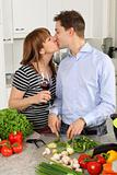 Young couple kissing in their kitchen