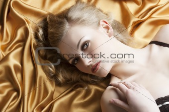 portrait of blond woman laying, she is turned of three quarters