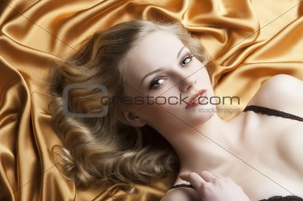 portrait of blond woman laying, she looks in to the lens