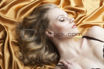 portrait of blond woman laying, she is turned in profile