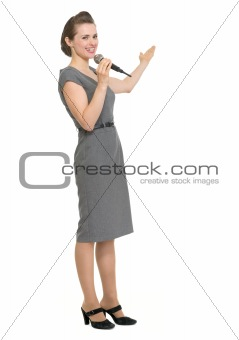 Woman reporter with microphone showing on copy space isolated
