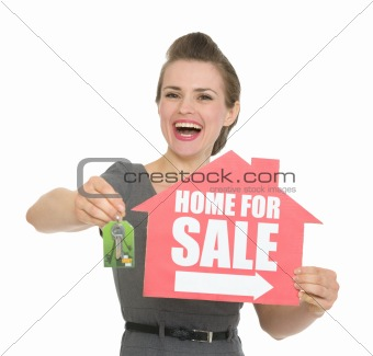 Happy woman holding home for sale sign and keys isolated