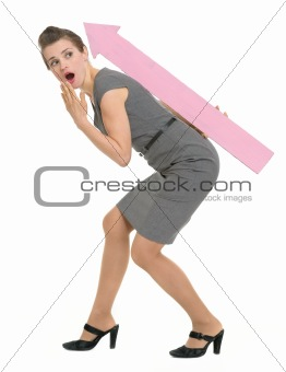 Surprised business woman carries on back big arrow pointing in corner isolated