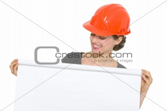 Smiling architect woman looking on blank flip chart isolated