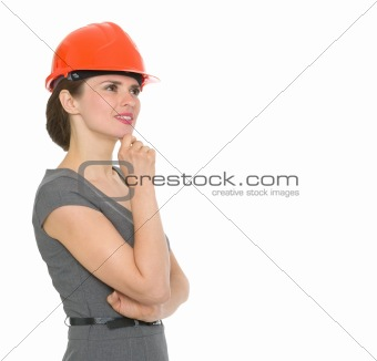 Portrait of dreaming architect woman in helmet looking on copyspace isolated