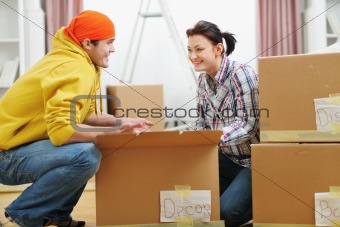 Moving young couple searching something in box