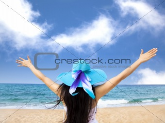 young woman raiseher hands up at the beach