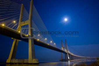 Suspension bridge under moonlight at night