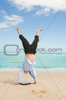 businessman doing handstand on the beach