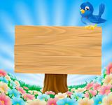 Bluebird sitting on wood sign with flowers