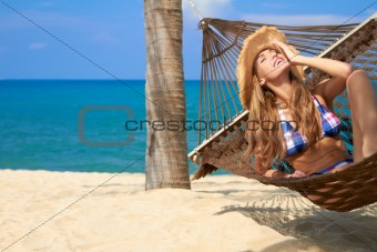 Attractive woman relaxing in a hammock