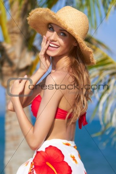 Happy young woman posing in straw hat