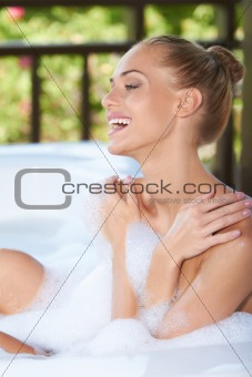 Laughing woman enjoying a bubble bath