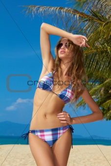 Female with beautiful body posing on beach
