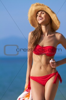 Smiling female in red bikini and straw hat