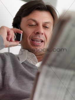 adult man reading stock exchange listings at home