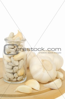 Garlic and herbal supplement pills isolated, alternative medicine concept