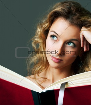 Woman holding book and dreaming. Copy space.