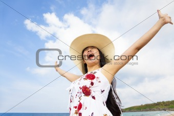 happy young woman raised hands on the beach
