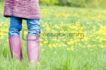 detail of woman wearing rubber boots on spring meadow