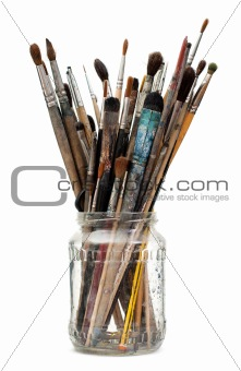 Assorted dirty old painting brushes in a glass flask