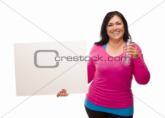 Attractive Middle Aged Hispanic Woman In Workout Clothes with Water Bottle and Blank White Sign Against a White Background.