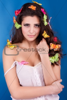 Beautiful girl with butterflies in hair poses in studio isolated on blue