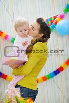 Mother kissing baby on birthday celebration party