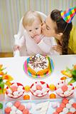 Mother kissing baby eating birthday cake
