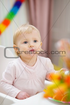 Portrait of thoughtful baby sitting at table