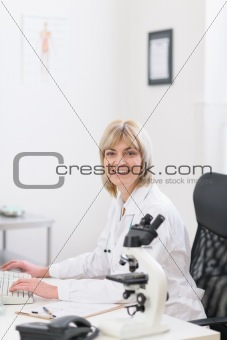 Smiling middle age doctor woman working at laboratory