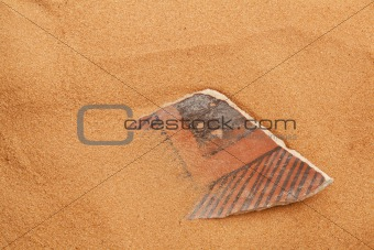 Anasazi pottery shard in red sand