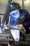 Manual welder welding in an industrial environment