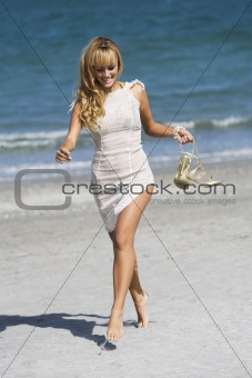 Pretty woman walking barefoot holding a pair of shoes
