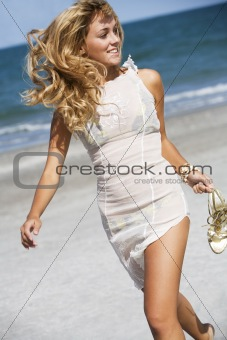 Beautiful blonde woman running on the beach
