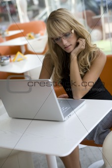 Attractive blonde woman working with a laptop in a cafe