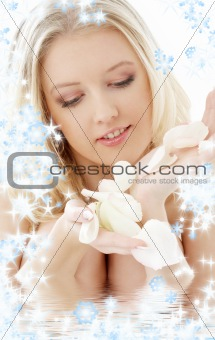 blond with white rose petals and snowflakes in water