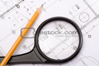 Small magnifier and pencil on a background of design drawings
