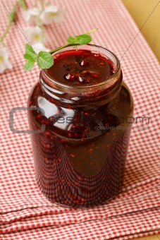 raspberry jam on a wooden table, rustic style