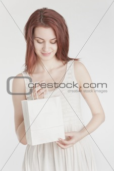Young woman holding a white shopping bag