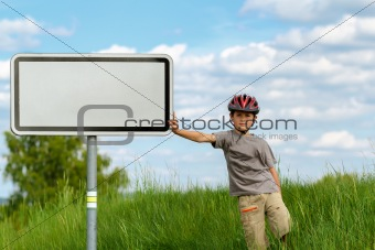 Boy cyclist leaning on blank sign