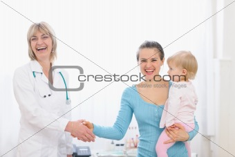 Happy mother holding baby and shaking hand to pediatric doctor
