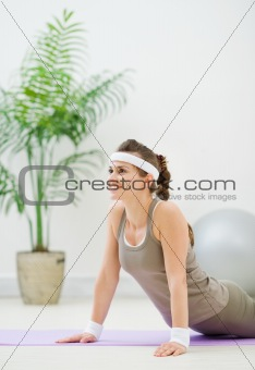 Fitness woman doing gymnastics exercises on floor