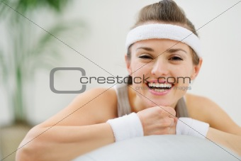 Portrait of happy healthy woman on fitness ball