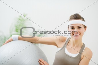Smiling woman holding fitness ball