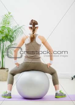 Slim woman sitting on fitness ball back to camera