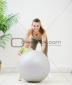 Portrait of mother and baby playing with fitness ball