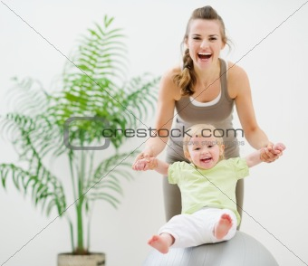 Mother and baby playing with fitness ball
