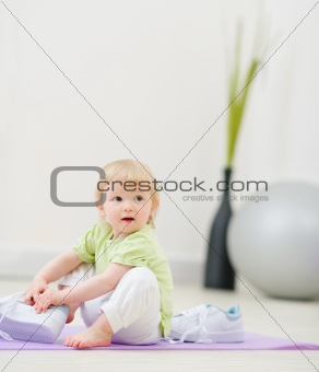 Baby trying to wear big sneakers