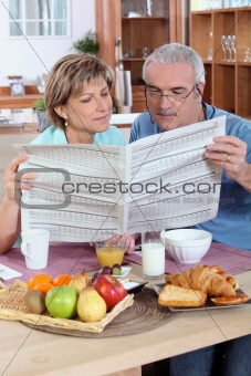 Couple reading the newspaper over breakfast